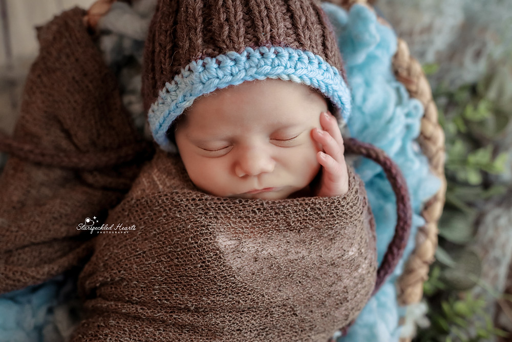 sleeping newborn baby boy wearing a brown knitted hat with turquoise trim, wrapped in a brown swaddle wrap, holding his hand to his cheek for his newborn photography session in aldershot hampshire near reading berkshire