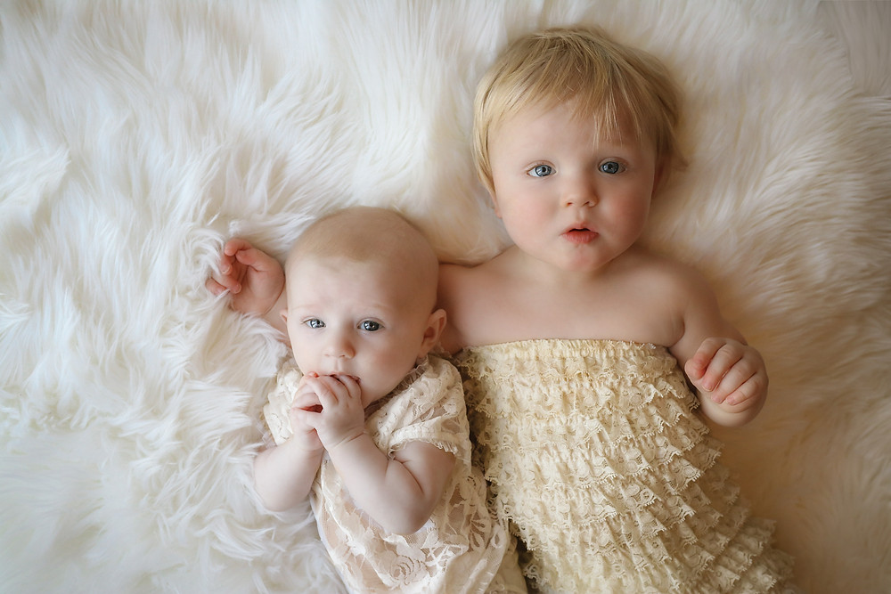 two baby girls wearing white lace laying on white fur rug