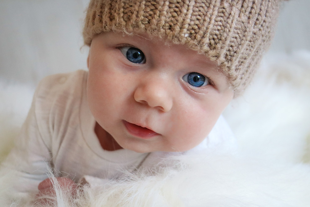 smiling baby boy with big blue eyes wearing a knitted hat, lying on his tummy on a white fur rug