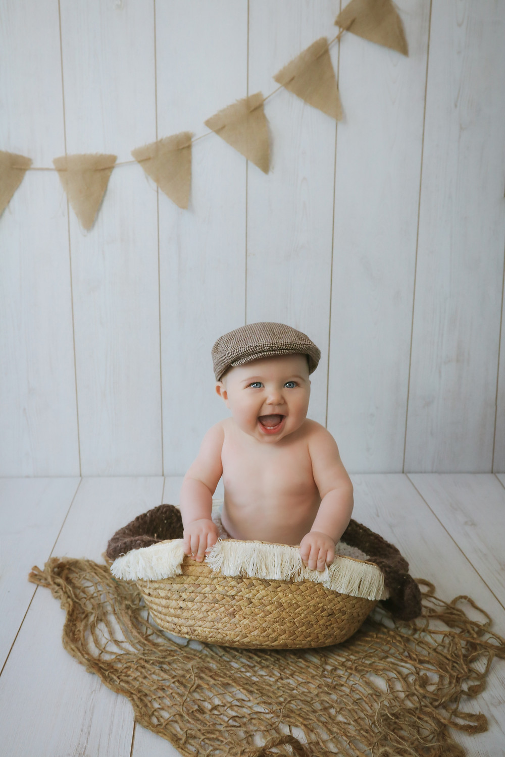 baby boy sitting up in basket laughing wearing flat cap