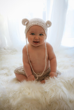 adorable baby boy wearing a knitted bear bonnet, sitting on a white fluffy rug