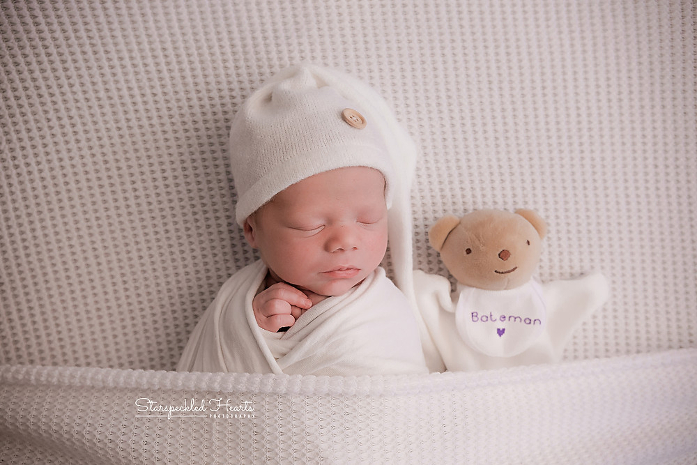 baby boy in white, tucked up with his teddy for his newborn session with starspeckled hearts photography