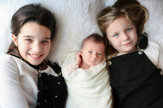 two older girls laying down on a white furry rug with a newborn girl between them
