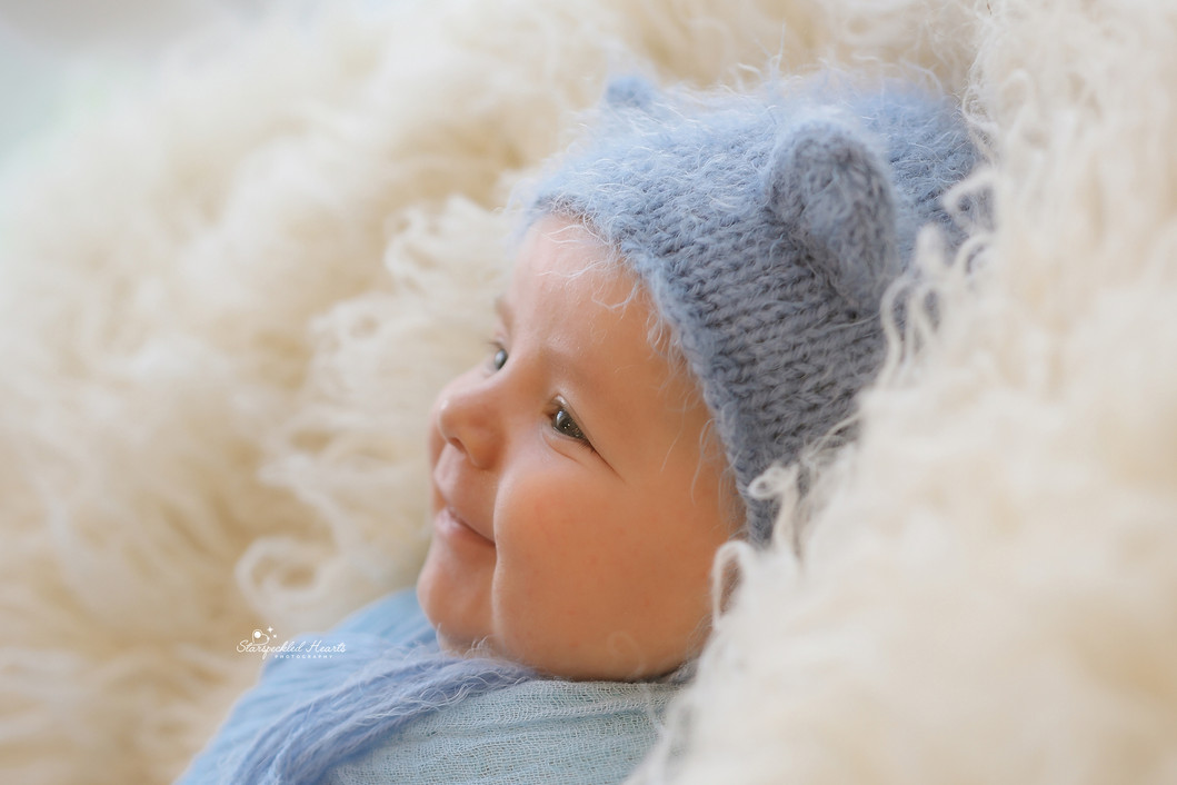 gorgeous baby boy with a big smile on his face, wearing a baby blue knitted bonnet