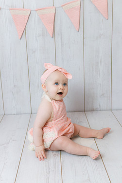 cute baby girl wearing a pale pink polkadotted romper suit, sitting in front of a white wooden wall panel with pale pink polka dotted bunting