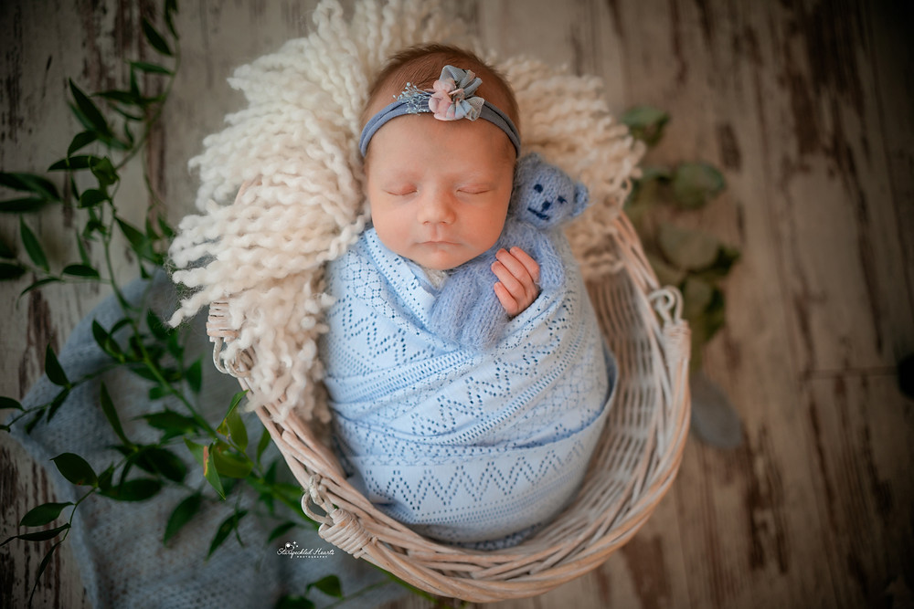 beautiful baby girl in blue, wrapped up in a wicker basket, cuddling a knitted teddy