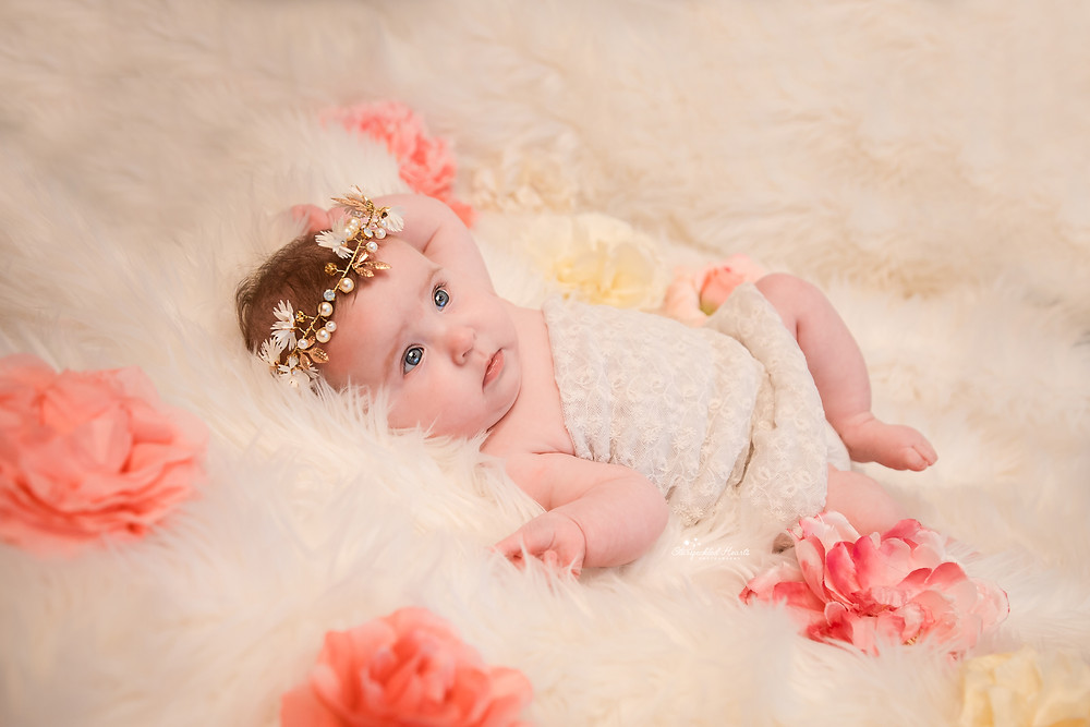 baby girl wearing a pearl crown and a lacy dress, lying on a white fluffy rug surrounded by pink flowers