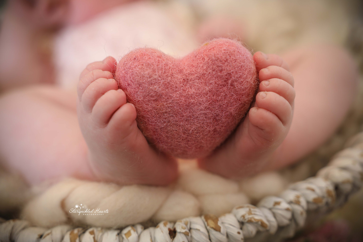 close up photo of baby feet holding a pink felted heart