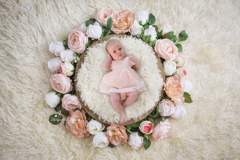 cute baby girl in a pink dress, laying in a floral wreath on a white rug
