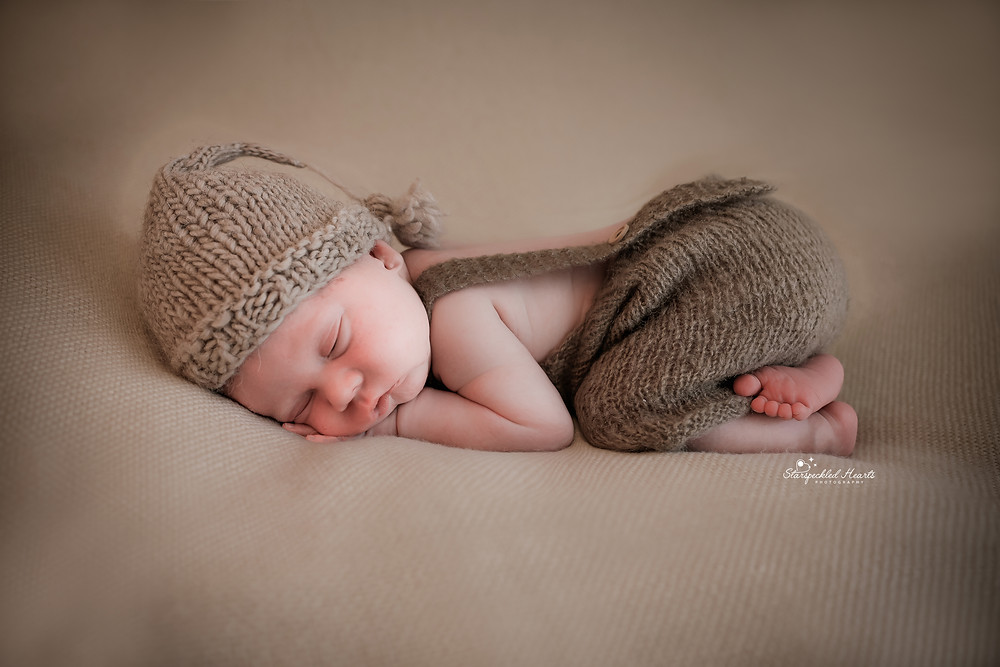 sleeping newborn wearing a knitted brown hat and dungarees in the bum up pose