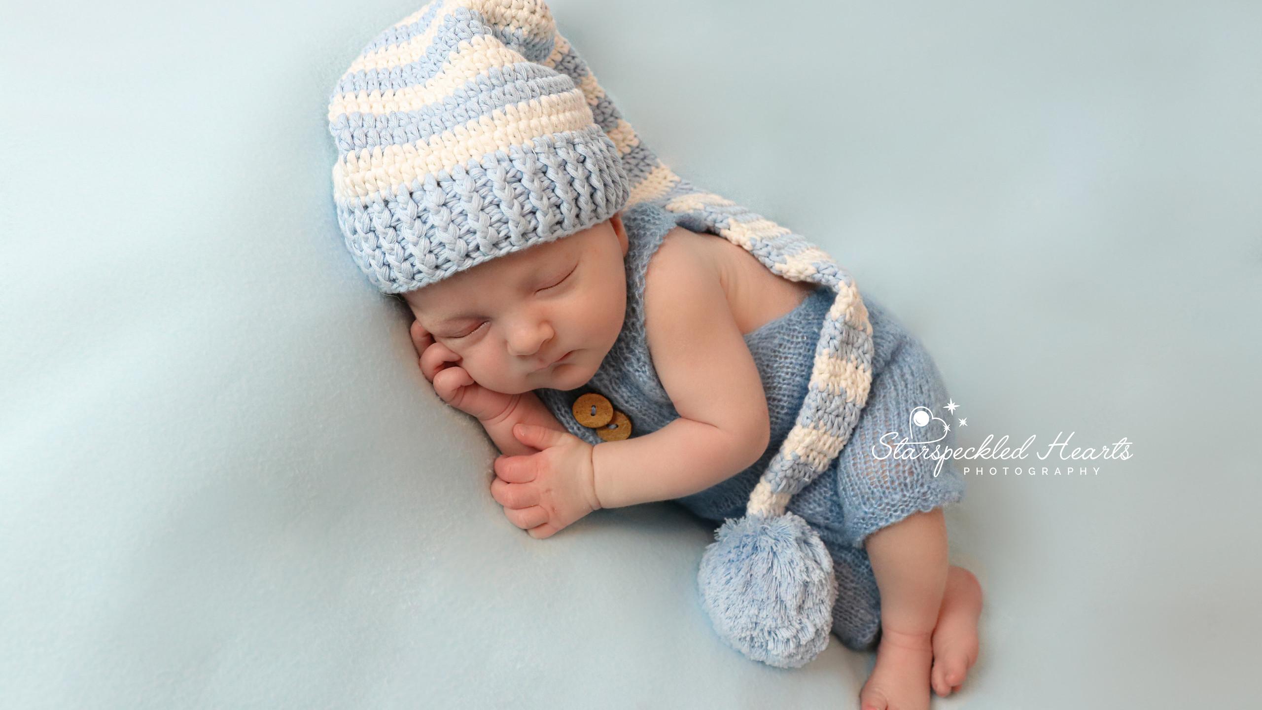 sleeping newborn lying on side wearing blue romper and blue striped hat