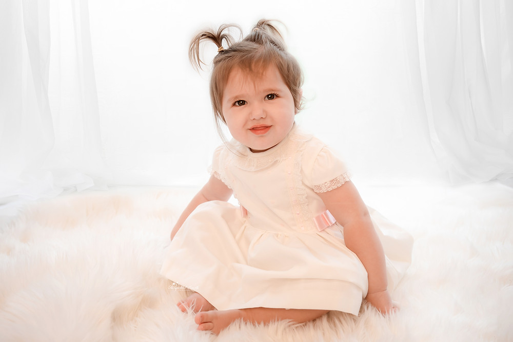 baby girl sitting on a white furry rug wearing a white lacy dress