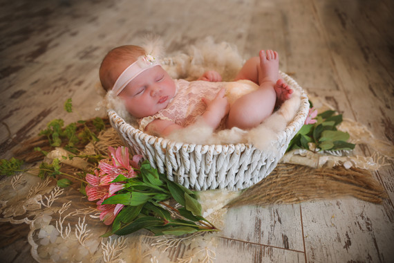 sleeping newborn baby girl, laying in a white wicker basket surrounded by flowers and greenery
