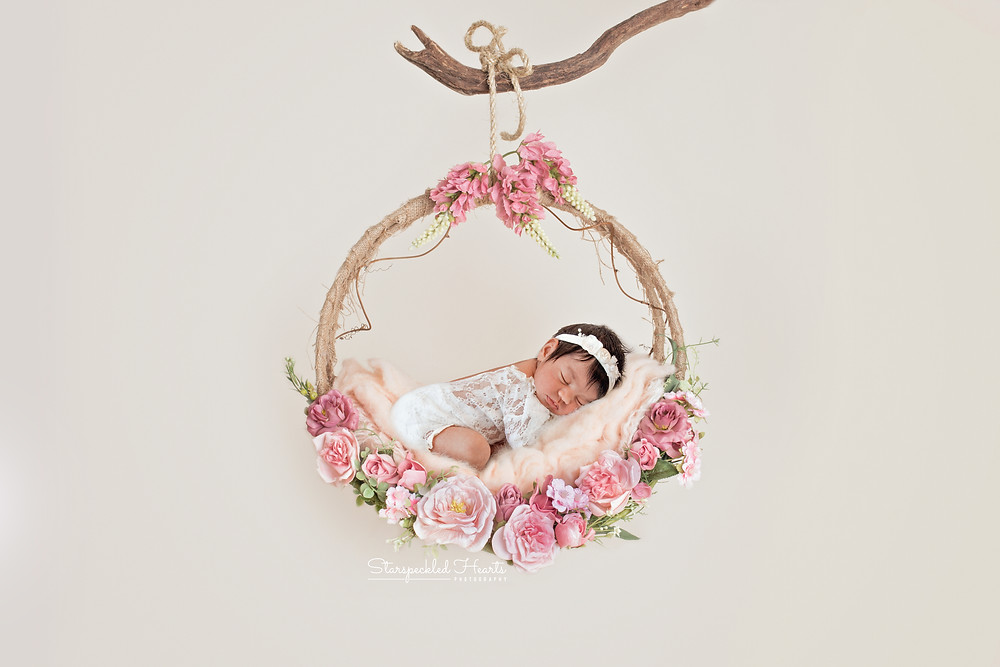 baby girl wearing a white lace romper, lying on a large swing surrounded by flowers
