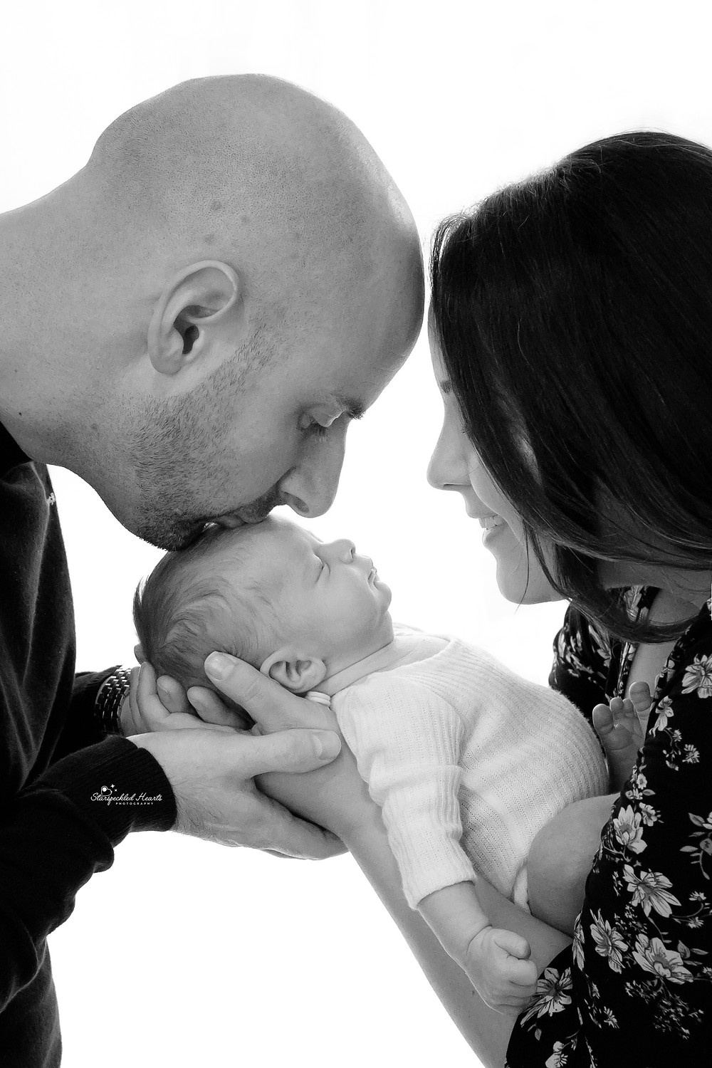 beautiful family, side profile shot of mum and dad looking down at their newborn son, held by mums hands