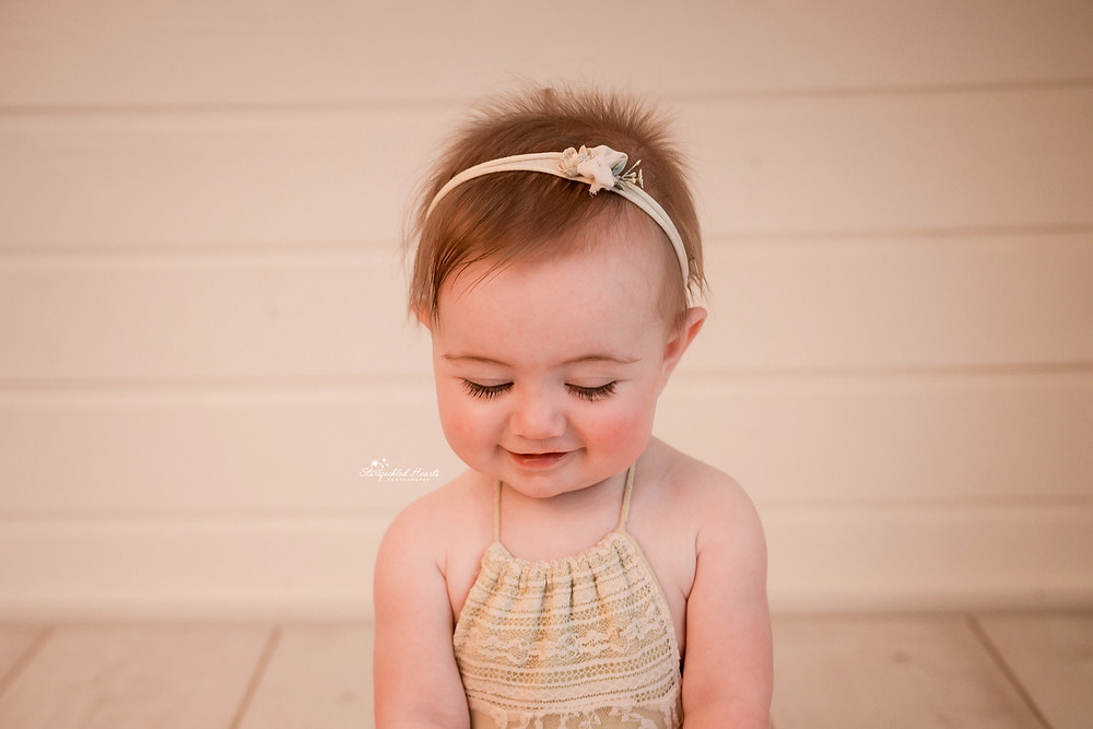close up of smiling baby girl with long eyelashes at her baby photography session with starspeckled hearts photography