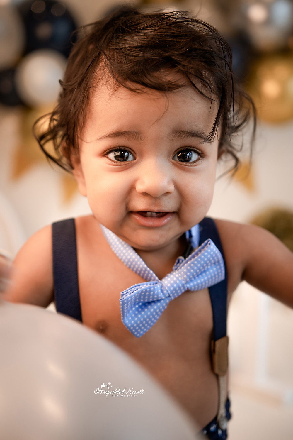bright eyed baby boy wearing a blue crown with a 1 on it and a matching bow tie for his cake smash session in hampshire
