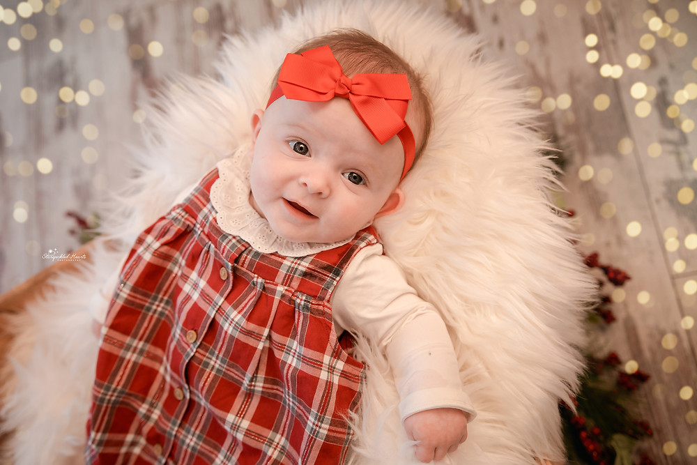 adorable baby girl wearing tartan and a red bow