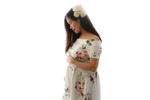 a pregnant woman with long black hair wearing a white floral gown and a floral headpiece, looking down at her pregnant baby bump