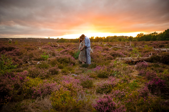 man and woman embracing standing in a floral meadow with the sun setting behind them