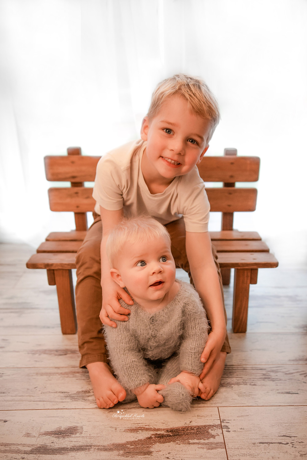 a young boy sitting on a bench with his baby brother sitting between his legs