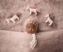 newborn wearing a pink bonnet, lying on a pink background with 3 felt unicorns over her head