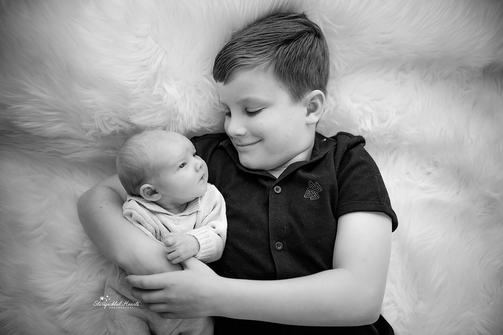 portrait in black and white of an older boy cuddling with his newborn brother, lovingly gazing at each other
