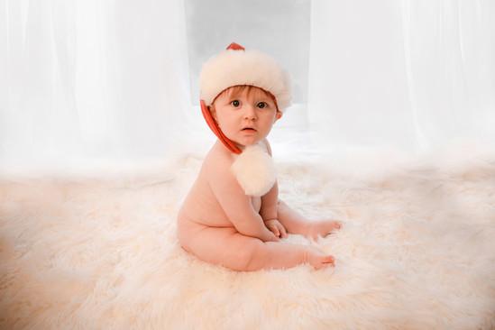 cute baby boy wearing a santa hat  sitting on a white fluffy rug