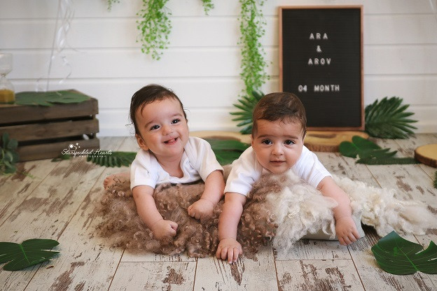 gorgeous twin boys lying on their tummies on a fluffy rug, with greenery and leaves behind them