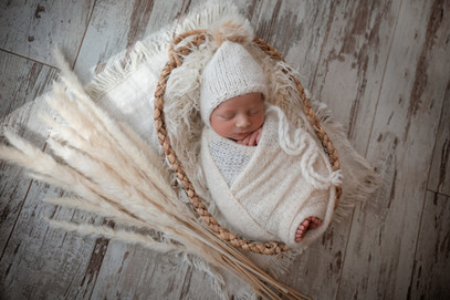 beautiful newborn baby boy wearing a white wrap, laying in an oval wicker basket for his newborn session with starspeckled hearts photography in aldershot hampshire