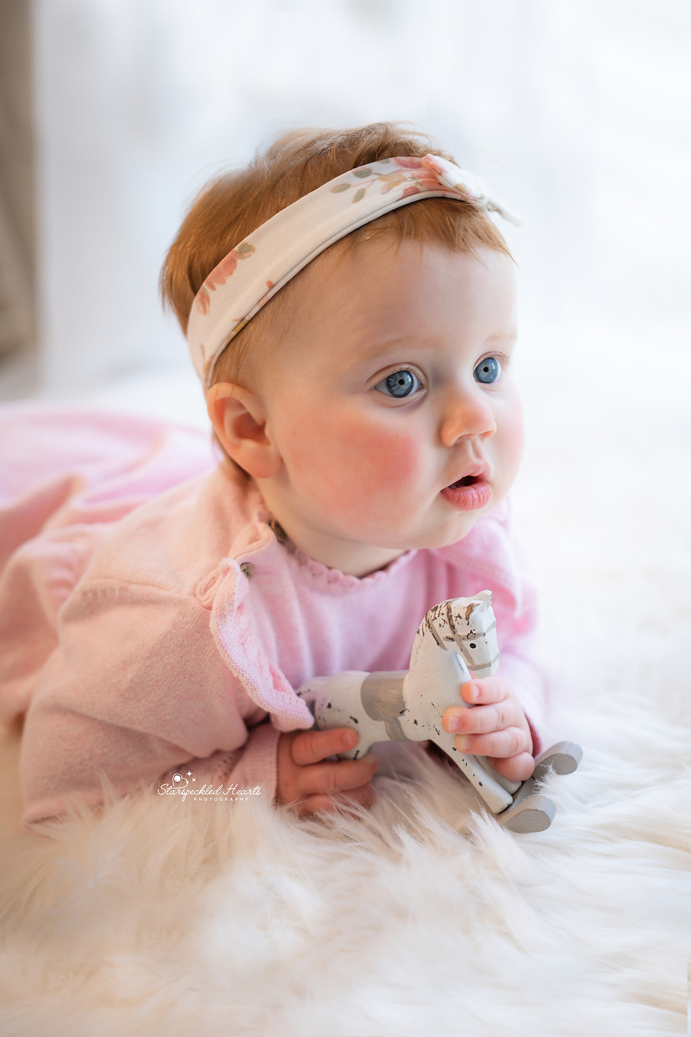 close up of baby girl with big blue eyes wearing a pink dress, cake smash photographer near me hampshire surrey