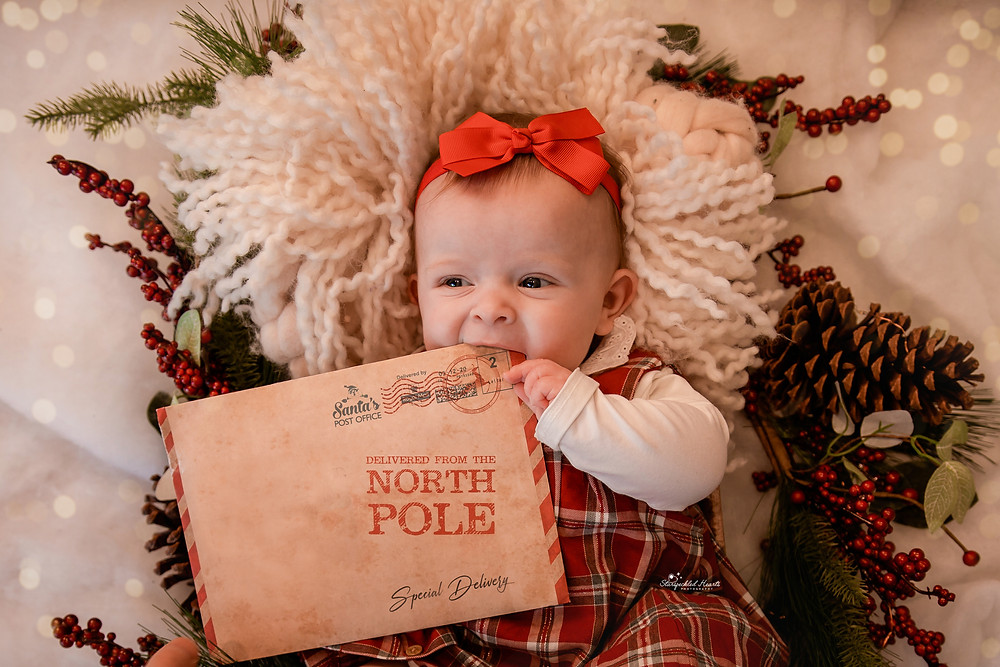 baby girl with a big, red bow wearing tartan holding a letter from the north pole