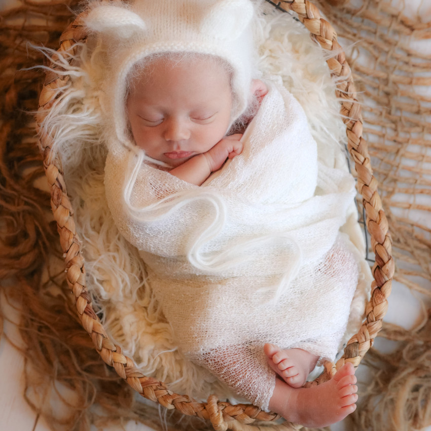 sleeping newborn wrapped in white