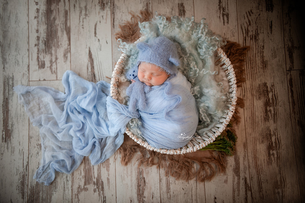 adorable sleeping newborn baby wrapped in blue, cuddling a white teddy bear