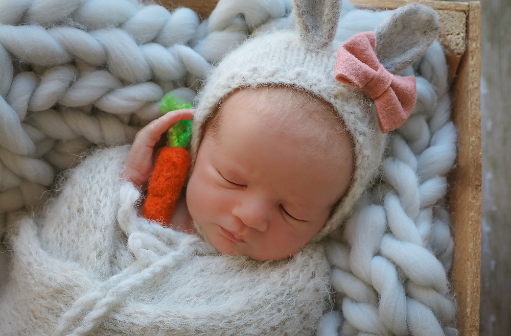 sleeping newborn wearing grey bunny bonnet holding felted carrot