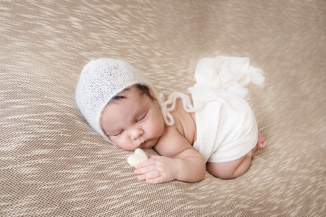sleeping newborn lying on his tummy wearing a white knitted bonnet holding a white felt heart
