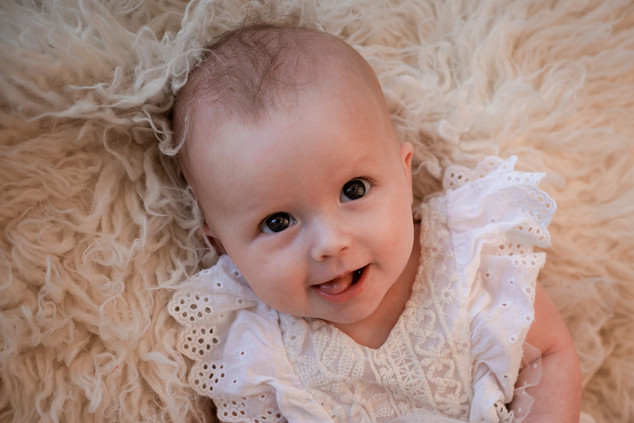 adorable baby girl smiling lying on a white furry rug