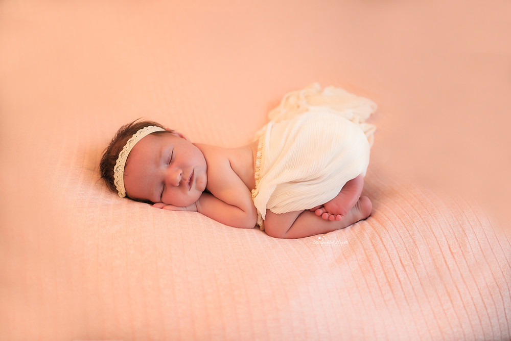 sleeping newborn girl lying on a pink backdrop with a white wrap draped around her