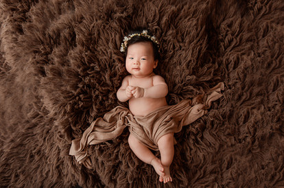 cute baby girl laying on a dark brown rug with a matching blanket over her for her baby photography session in aldershot, hampshire