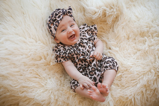 smiling baby girl wearing a leopard print and matching turban romper suit