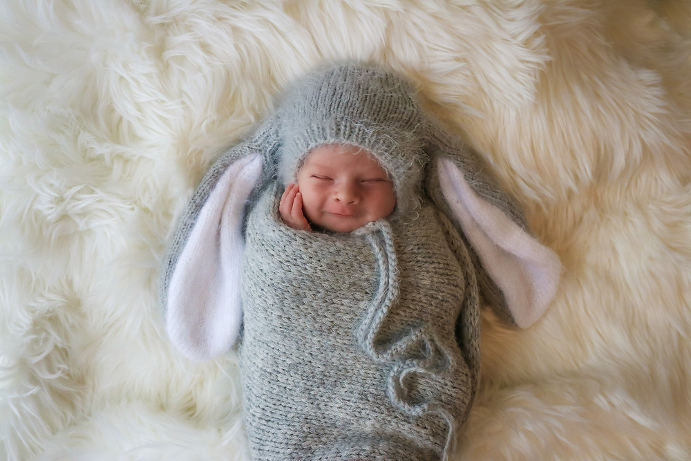 beautiful smiling sleeping baby wearing a grey bunny bonnet and matching grey wrap, lying on a white fluffy rug
