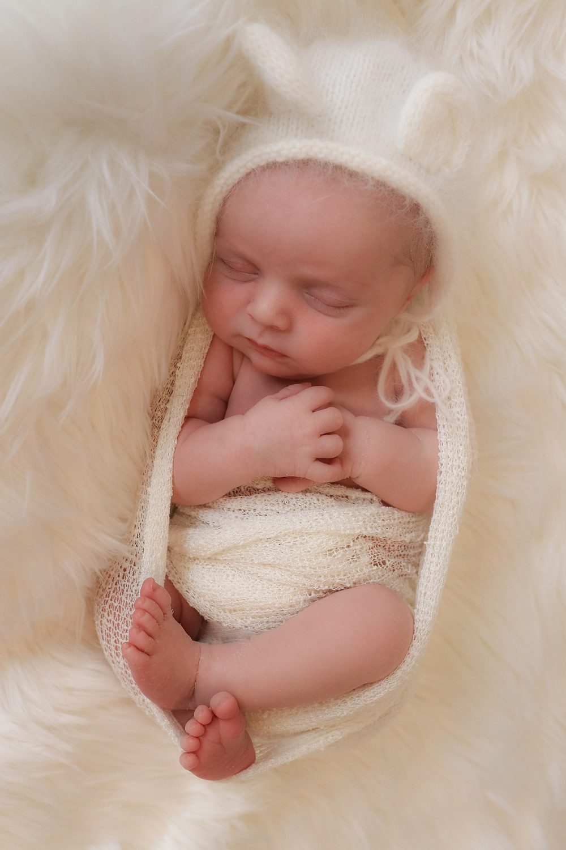 sleeping newborn curled up wearing white