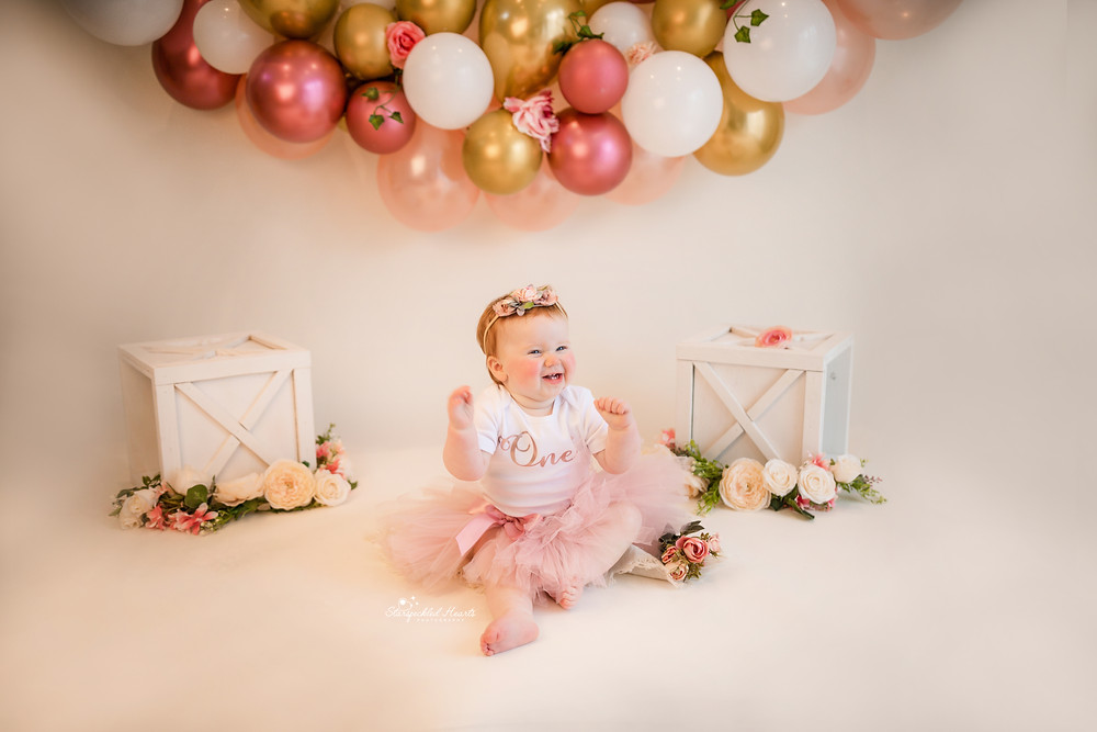 girly 1st birthday cake smash session with pink gold and white balloons for adorable baby girl in aldershot hampshire