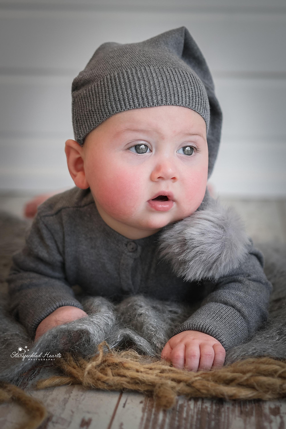 gorgeous baby boy wearing a grey hat with a pompom on the end