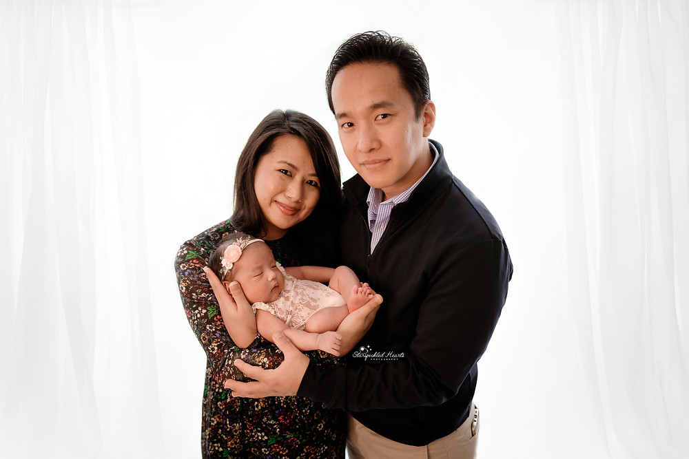 family portrait of a mother and father holding their newborn baby girl in their arms