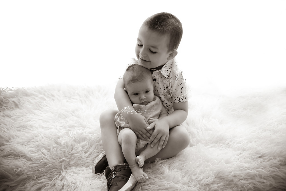 baby boy sitting on a white fluffy rug, holding his baby sister
