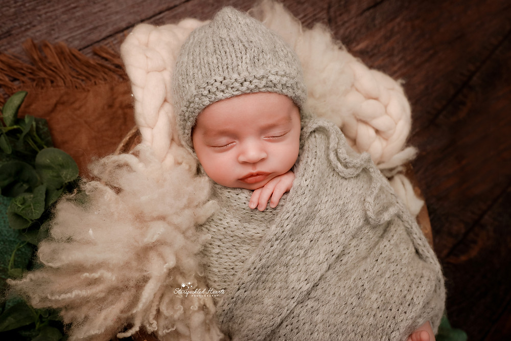 newborn baby wrapped in a grey knitted swaddle wrap and bonnet set, lying in a brown wooden crate fast asleep for his newborn photoshoot with starspeckled hearts photography