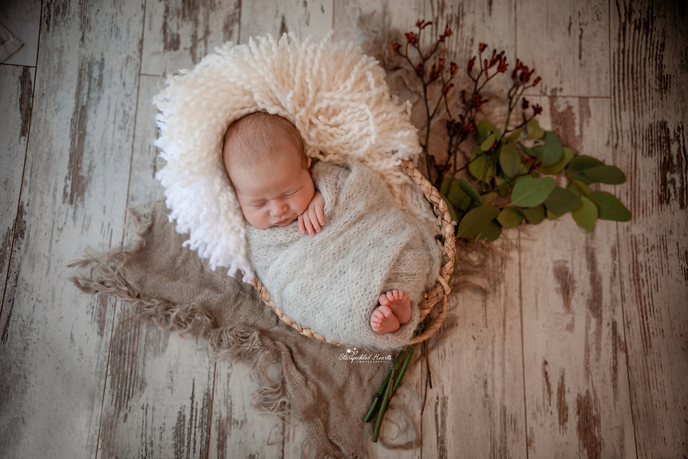 adorable sleeping newborn baby boy wrapped in grey lying in a wicker basket