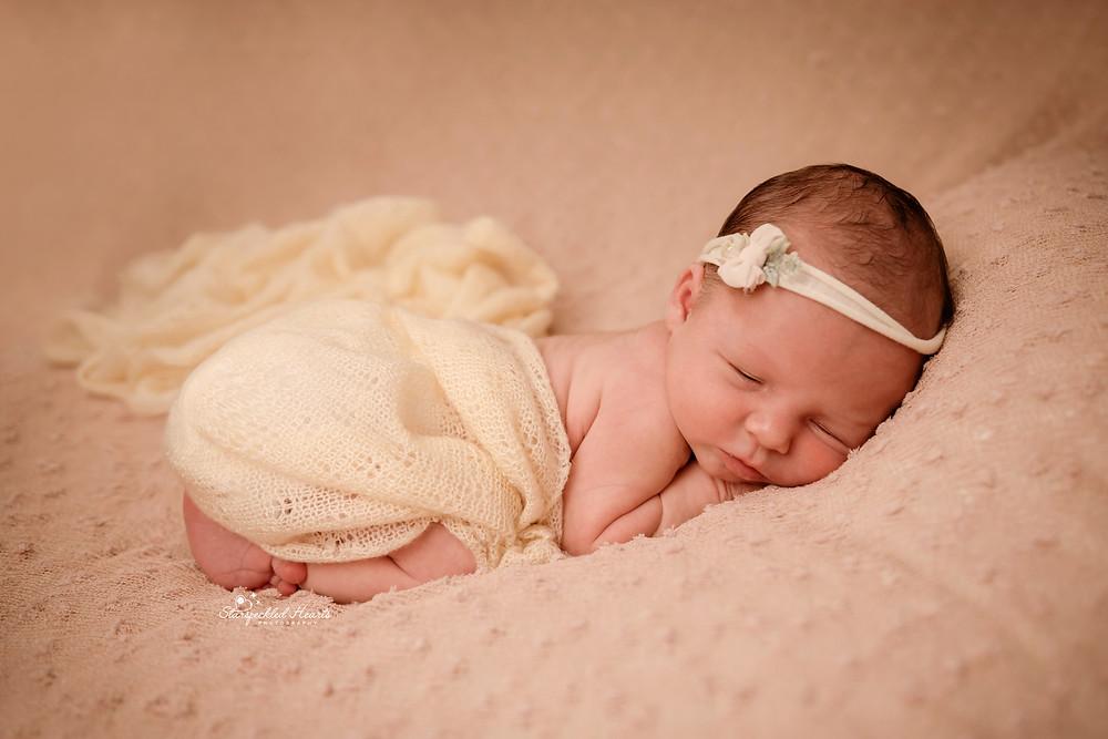 sleeping newborn girl lying on a pink textured blanket