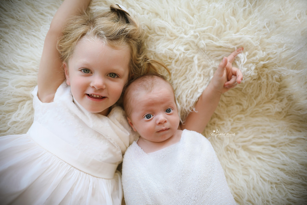 a little girl and her newborn baby brother laying next to each other on a white fluffy rug, both wearing white